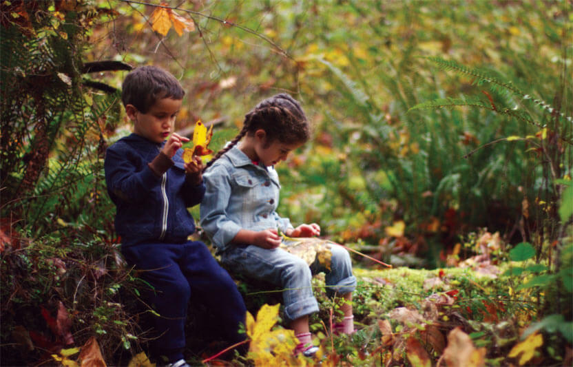 Boy and Girl playing outside with fall leaves